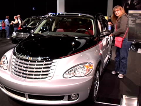 front three-quarter driver side view of pt cruiser couture edition; woman looks inside; gets in car / passenger side profile 2010 chrysler pt cruiser... - three quarter length stock videos & royalty-free footage