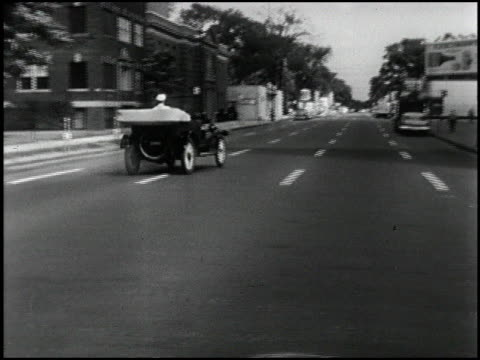 front three-quarter passenger side tracking shot of 1914 chevrolet driving on the 1957 streets of detroit; driver hand signals a left turn and turns... - dreiviertelansicht stock-videos und b-roll-filmmaterial