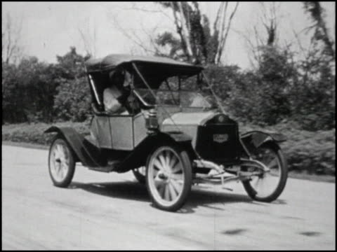 stockvideo's en b-roll-footage met / ws front threequarter tracking shot of 1909 flanders roadster in black and white / as car continues to drive picture dissolves to full color 1909... - 1900 1909