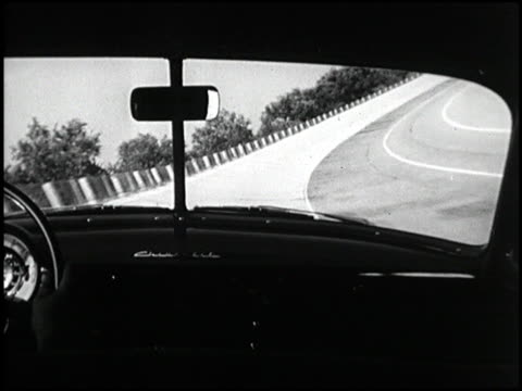 ws front threequarter tracking shot of 1949 chevrolet deluxe styleline sedan driving on banked track / ms pov through front windshield of chevy... - tre quarti video stock e b–roll