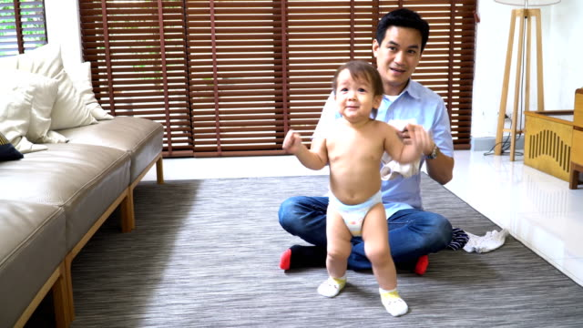 front view: 2 year old son getting dressed from his young father - genderblend stock videos & royalty-free footage