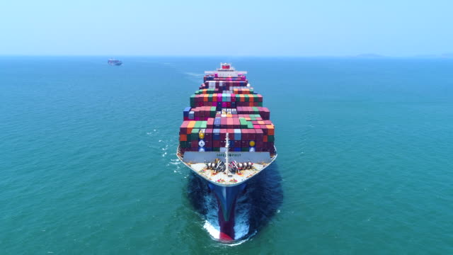 vídeos de stock e filmes b-roll de 4k front view : aerial view container ship full load container on the green sea for logistics , shipping , import export or transportation. - navio cargueiro