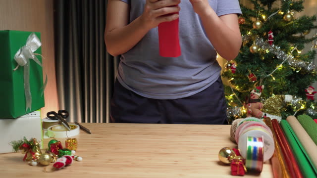 front view: asian woman's hand preparing the gift,  wrapping christmas presents from a gray paper box with red paper on the table at home at night with christmas tree decorated with ornament. - christmas wrapping paper stock videos & royalty-free footage