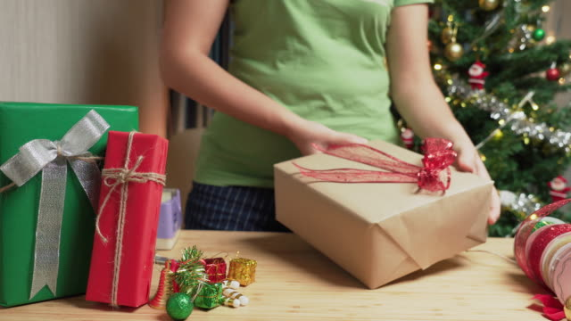 front view: asian woman's hand preparing the gift,  wrapping christmas presents from a gray paper box with brown paper, and attaching red ribbon on the table at home at night with christmas tree decorated with ornament. - christmas wrapping paper stock videos & royalty-free footage