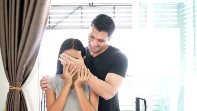 front view: Attractive young couple is moving, standing in an empty home. Man is covering his woman eyes making a surprise