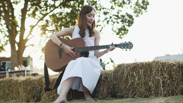 front view beautiful young asian woman in white dress is playing guitar on a haystack in the morning sunlight lens flare. - white dress stock videos & royalty-free footage