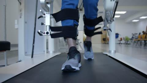 vidéos et rushes de vue avant près de l'homme marchant à l'aide d'un robot exosquelette sur le tapis roulant - rétablissement