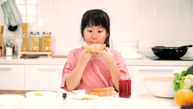 front view: cute asian girls eating her toast with strawberry jam that she make it by herself for having breakfast - morning breakfast stock videos & royalty-free footage