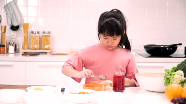 front view: cute asian girls preparing her toast with strawberry jam by herself for having breakfast - strawberry jam stock videos & royalty-free footage