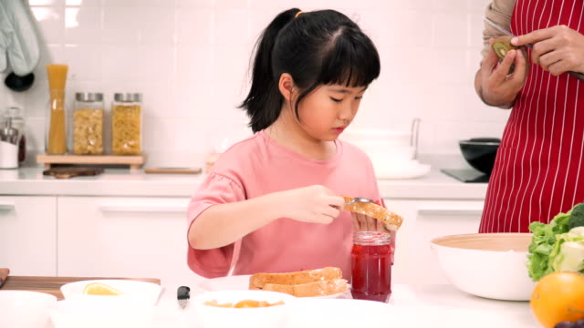 front view: cute asian girls preparing her toast with strawberry jam by herself for having breakfast with his father - strawberry jam stock videos & royalty-free footage