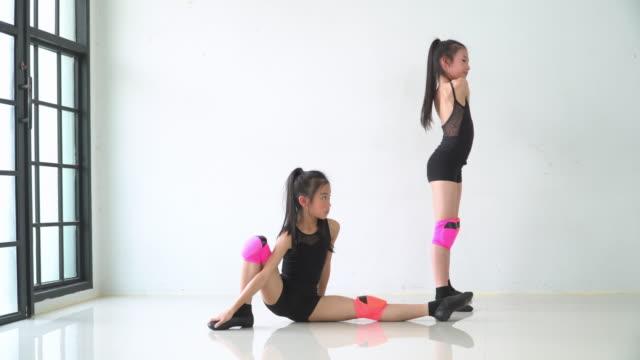 正面図:彼女の足を伸ばすかわいい女の子のダンサーと別の作るブリッジポーズ - 弓のポーズ点の映像素材/bロール