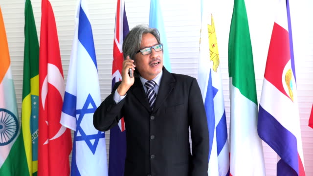 front view: dignified and old businessman communicate with colleague on smartphone on national flag - uruguaian flag stock videos & royalty-free footage