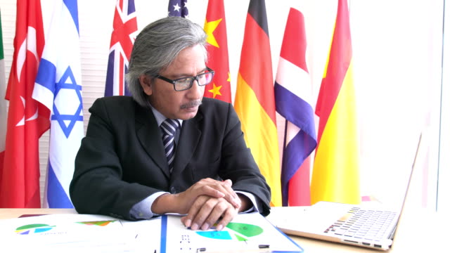 front view: dignified and old businessman thinking and making conference on notebook on national flag - bandiera dell'argentina video stock e b–roll