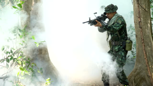 vídeos de stock e filmes b-roll de front view: face of group of fully equipped and armed soldier appear form mist while  patrolling in tropical forest - metralhadora
