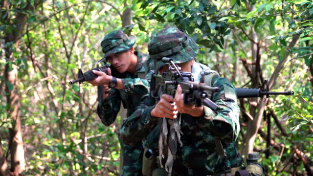 front view: face of group of fully Equipped and Armed Soldier patrol in tropical forest