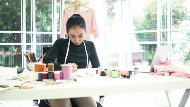 vídeos de stock, filmes e b-roll de vista frontal: projeto de designer de moda feminina e escrever no escritório em casa - 20 29 years