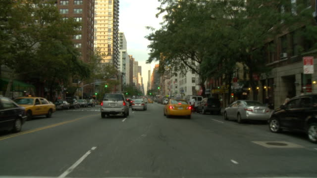 POV Front view from car driving down street with traffic / New York City, New York, United States