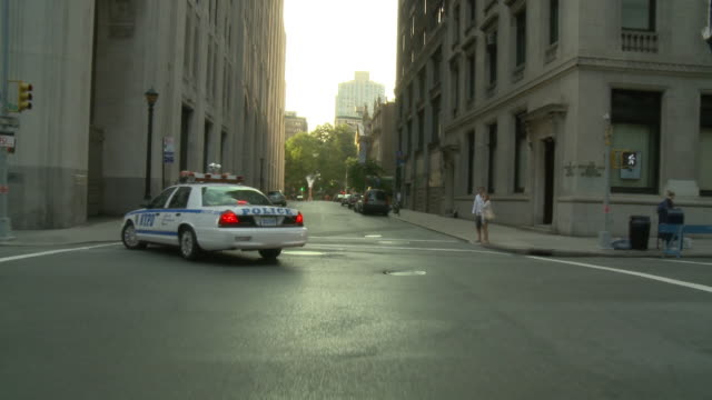 POV Front view from car turning a corner after a police car / New York City, New York, United States