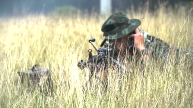 front view: Fully Equipped and Armed Soldiers talking on his phone while being ready to fight