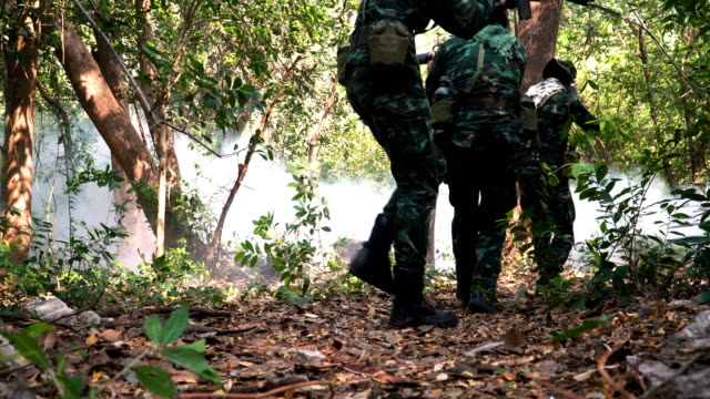 front view: group of fully Equipped and Armed Soldier are going to fight in tropical forest