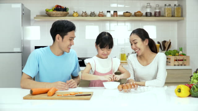 front view: her young parent looking daughter cooking by herself in kitchen - wife stock videos & royalty-free footage