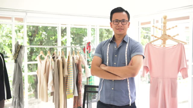 vídeos de stock e filmes b-roll de front view: male fashion designer is proud of his job by smiling in home office - 30 34 years