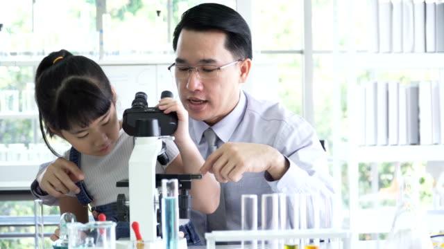 正面: 男性教師は、化学実験を行うための光学顕微鏡を使用する女の子を教える - chemistry点の映像素材/bロール