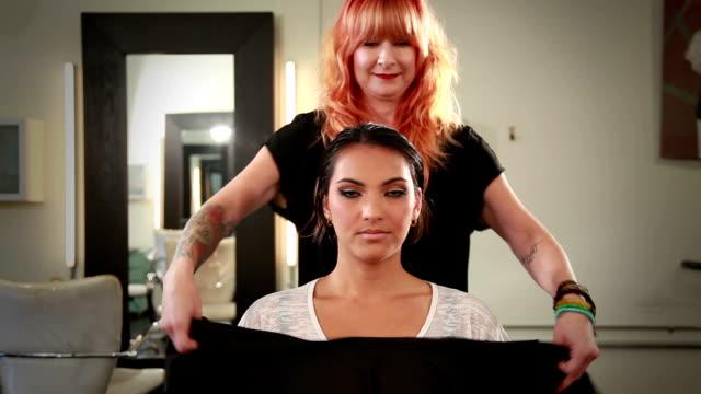 vídeos de stock e filmes b-roll de vista frontal do plano médio da bela jovem mulher em um salão de cabeleireiro - salão de beleza