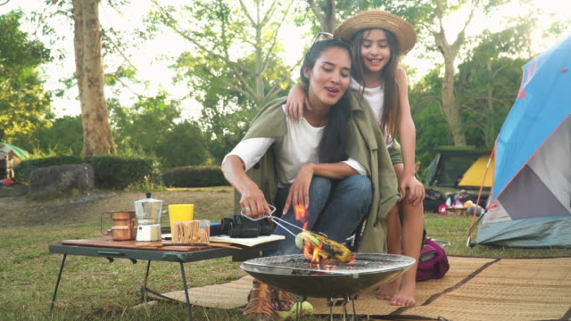 front view: mother and daugther spend weekend time having picnic together and cooking bbq - camping stock videos & royalty-free footage