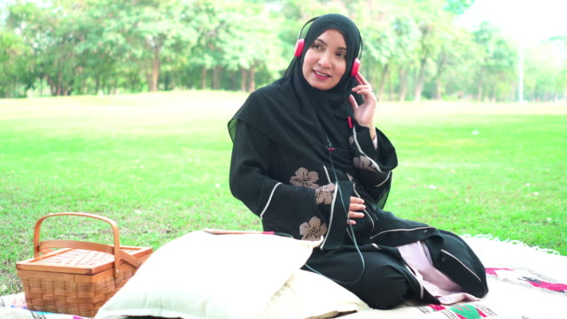 front view:  muslim asian pregnant wearing a religious dress called hijab with feeling love and happiness, wearing headphones to make positive emotion for the fetus, and touching belly on the carpet at public park for weekend activities. - religious dress stock videos & royalty-free footage