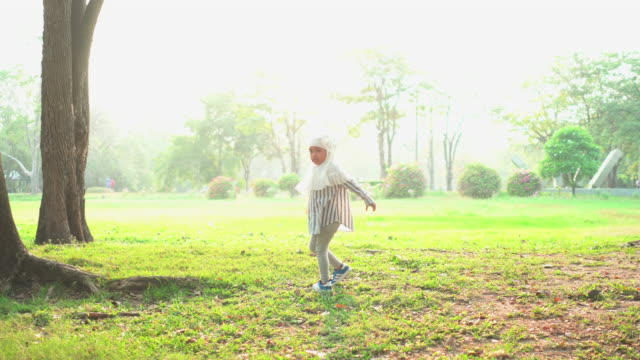 front view:  muslim asian teenage girl wearing a religious dress called hijab with feeling love and happiness, looking at a view of the public park under sunlight and walk from fame. the concept of picnic with positive emotion and weekend activities - religious dress stock videos & royalty-free footage