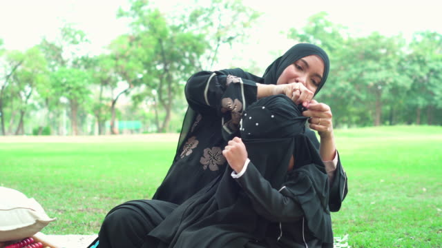 front view:  muslim asian teenage girl wearing a religious dress called hijab with feeling love and happiness from mother sitting on the carpet at public park for weekend activities. the concept of religious people having a picnic with positive emotion. - religious dress stock videos & royalty-free footage