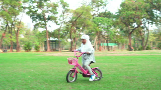front view:  muslim asian teenage girl wearing a religious dress with feeling love and happiness, riding a bike at public park for weekend activities. the concept of picnic with positive emotion. - religious dress stock videos & royalty-free footage