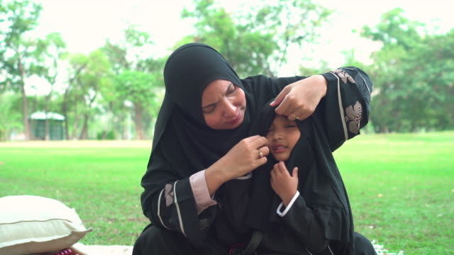front view:  muslim asian teenage girl wearing a religious dress with feeling love and happiness from mother sitting on the carpet at public park for weekend activities. the concept of religious people having a picnic with positive emotion. - religious dress stock videos & royalty-free footage