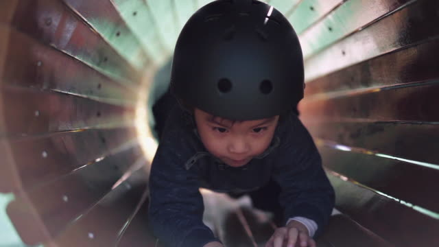 stockvideo's en b-roll-footage met front view of a boy wearing sports helmet playing at playground - speeltuin