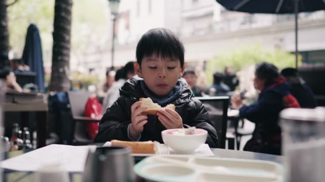 front view of a little boy eating bread in restaurant, xintiandi, huangpu district, shanghai, china - baby boys stock videos & royalty-free footage