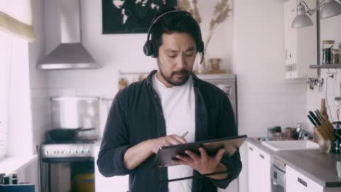 vídeos de stock, filmes e b-roll de a vista dianteira de um homem asiático usa a tabuleta digital durante a chamada de conferência - 35 39 anos