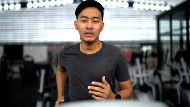 front view of asian man running on treadmill in gym - health club stock videos & royalty-free footage