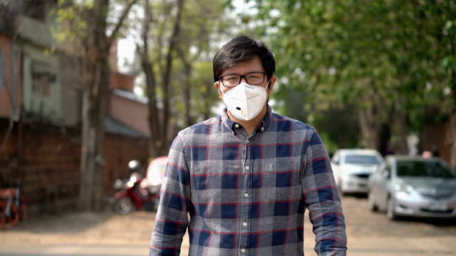 front view of asian man wearing air pollution mask walking in the city, chiang mai, thailand - casual clothing stock videos & royalty-free footage