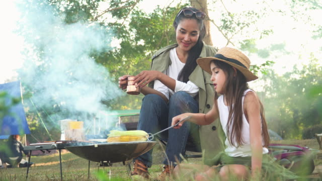 front view of asian mother and mixed-race daughter travel camping together in a forest, happy and relaxed woman and teenage girl cooking bbq is in front of a tent. concept of adventure family at the weekend. - travel destinations stock videos & royalty-free footage