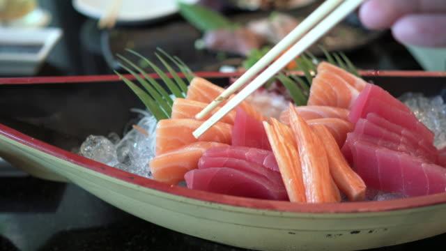 vídeos de stock, filmes e b-roll de vista frontal da mão segurando os pauzinhos tomando sashimi de salmão fresco - sashimi