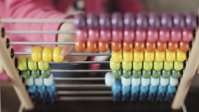 front view of little cheerful girl playing with abacus at home stock video... - genius stock videos & royalty-free footage