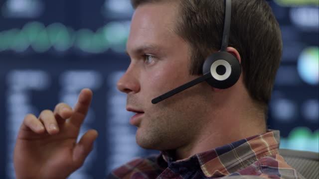 vídeos y material grabado en eventos de stock de front view of man listening and talking on headset. - centro de llamadas