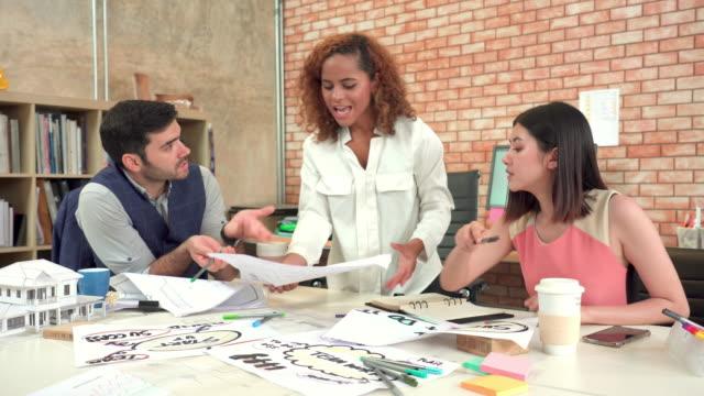 vidéos et rushes de vue avant de la salle de réunion dans le bureau moderne d'architecturale, les belles femmes d'affaires européennes ou l'architecte créateur debout, partageant, discutant, et la stratégie d'affaires de remue-méninges avec des collègues asiatiq - trois personnes
