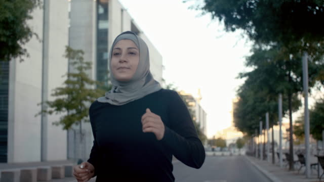 front view of muslim woman in hijab running in berlin (slow motion) - one young woman only stock videos & royalty-free footage