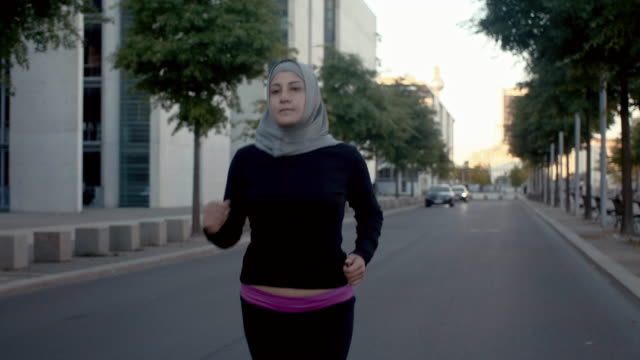 front view of muslim woman in hijab running in berlin (slow motion) - hijab stock videos and b-roll footage