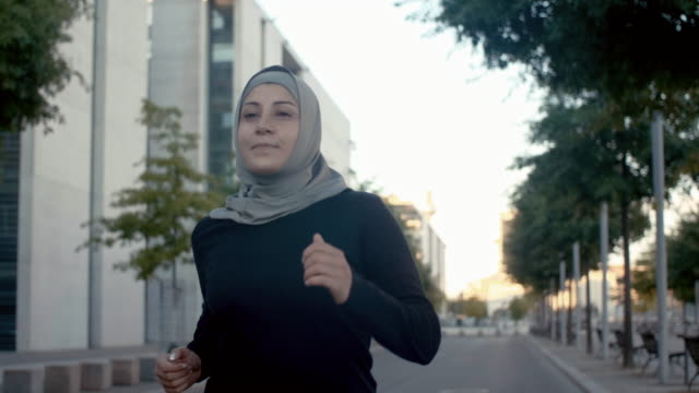 front view of muslim woman in hijab running - islam stock videos & royalty-free footage