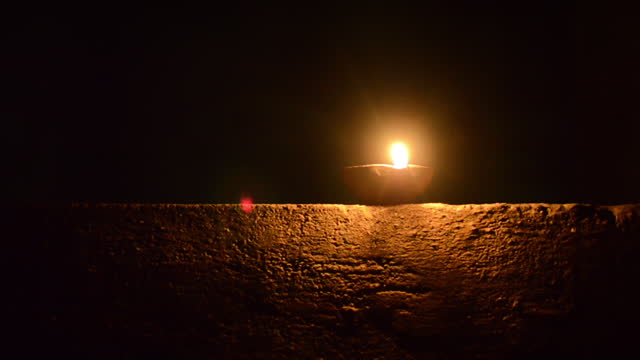 front view of one burning candle (oil candle / oil lamp / clay lamp) on an old wall glowing the surface of wall below it and black background at the rest of the parts with copy space - candlelight stock videos & royalty-free footage