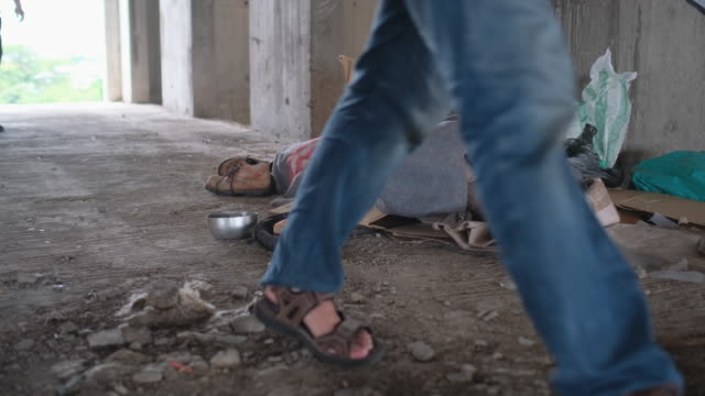 front view of one walking people give money to elderly homeless man who lie on floor of abandoned building in city - 物を乞う点の映像素材/bロール