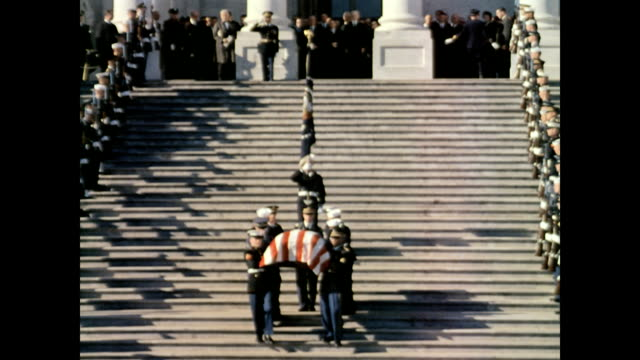 vídeos de stock e filmes b-roll de front view of president john f kennedy's coffin being carried from the capitol building / pallbearers walk slowly down the steps / place coffin on... - morte